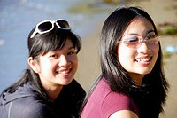 2 asian girls together at the beach smiling, sisters