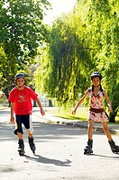 Boy and girl (10-12) inline skating in park,wearing protective helmets