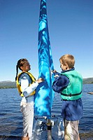 Girl and boy (13-15) opening sail of small boat at side of lake