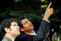 2 young business men pointing and having dicussion