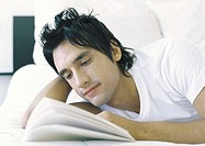 Man lying in bed, reading