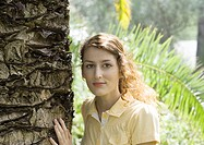 Woman standing with hand on tree trunk, smiling at camera