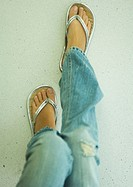 Young woman wearing flipflops, low section