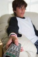 Boy (12-13) sitting on sofa, holding remote control