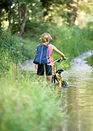 Girl walking through water with bike, rear view