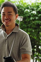 Man holding golf club, smiling at camera