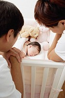 Mother and father leaning on crib looking down at sleeping baby