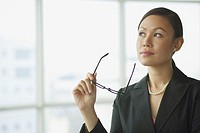 Businesswoman looking away, holding glasses