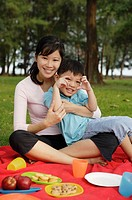 Mother and son on picnic blanket, smiling at camera