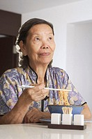 Senior woman having noodles at home, looking away