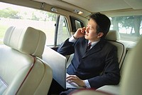 Businessman in car, using laptop and mobile phone