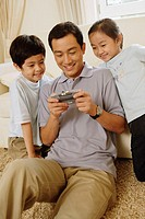 Father playing hand held game, two children next to him