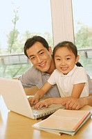 Father and daughter with laptop, smiling at camera