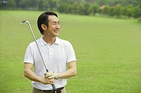 Man holding golf club, smiling, looking away