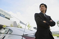 Businessman with arms crossed, leaning on car, looking away