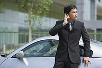 Businessman using mobile phone, leaning on car