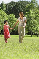 Mother and daughter, holding hands, walking on grass