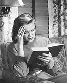 Woman reading book, touching forehead, (B&W)
