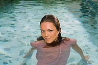 Young woman wearing clothes in pool, portrait, close-up