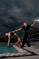 Young couple dancing by pool, night, side view