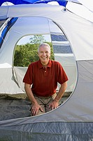 Mature man kneeling in a tent