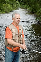 Mature man fishing in a stream