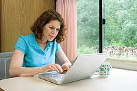 Woman using a laptop computer in caravan