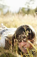 young woman lying in meadow, close-up