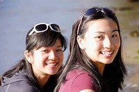 2 asian girls sitting together on beach