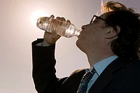 Businessman drinking from water bottle