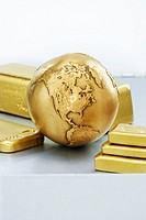 Golden globe and gold ingots of different sizes