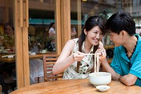 Young couple sharing noodles
