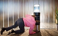 Businessman Kneeling to Drink from Water Cooler