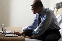 Businessman using a laptop on bed