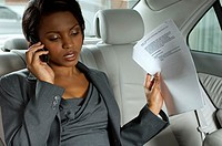 Businesswoman talking on cell phone in backseat