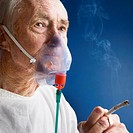 Elderly Patient Wearing Oxygen Mask and Smoking Cigarette
