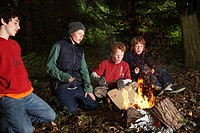 Four Boys Sitting Around Campfire