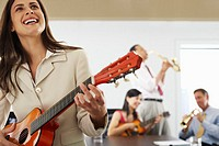 Businesspeople Making Music in Conference Room