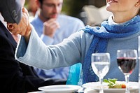 Woman Shaking Hands at Table