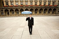 Businessman Holding Umbrella in Square