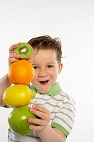 Boy Playing With Stack of Fruit
