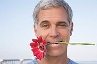 Man Holding Flower Between his Teeth