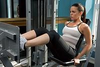 Woman Using Leg Press at Health Club
