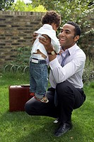 Businessman Hugging Baby Boy in Garden