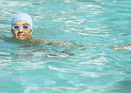 Person wearing bathing cap and goggles in pool
