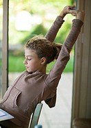 Preteen girl sitting at desk, stretching arms over head