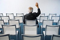 Businessman Raising Hand in Auditorium
