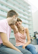 Teen couple sitting in urban area, smiling at each other