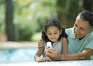 Mature man showing granddaughter cell phone