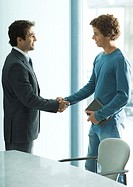 Businessman shaking hands with casually dressed yound adult male